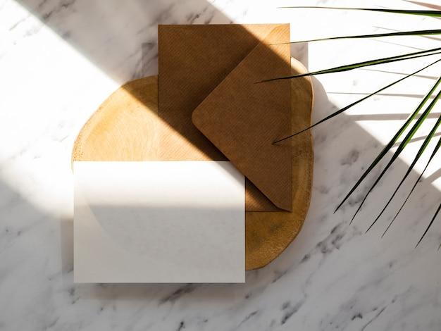 Enveloppe brune avec un blanc sur une plaque de bois sur un fond en marbre avec des feuilles vertes Photo gratuit