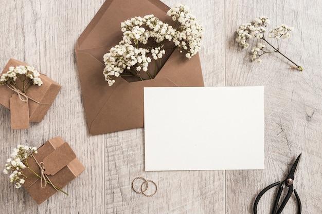 Enveloppe brune avec des fleurs d'haleine de bébé; coffrets cadeaux; anneaux de mariage; carte ciseaux et blanc sur fond en bois Photo gratuit