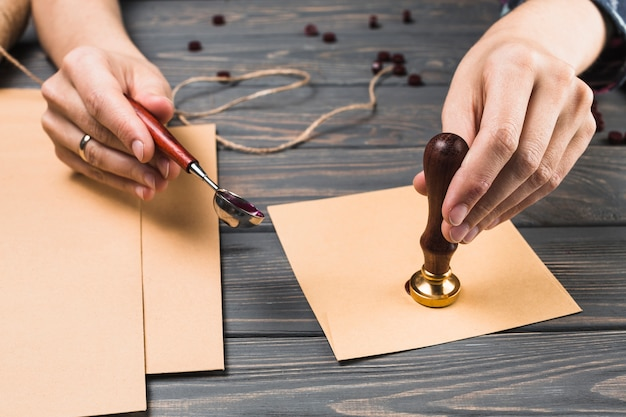 Enveloppe de cachetage de la main de femme avec timbre Photo gratuit