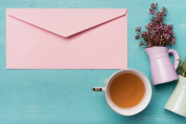Enveloppe fermée rose avec une tasse de thé et vase sur un fond en bois bleu Photo gratuit