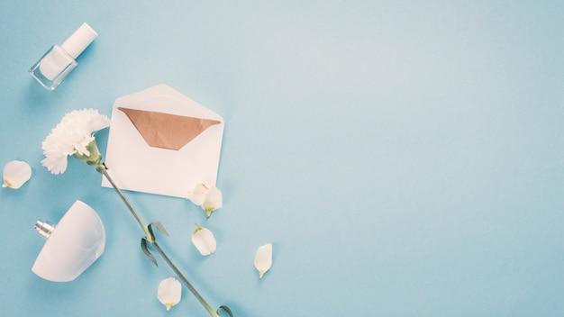Enveloppe avec fleur blanche et parfum sur table Photo gratuit