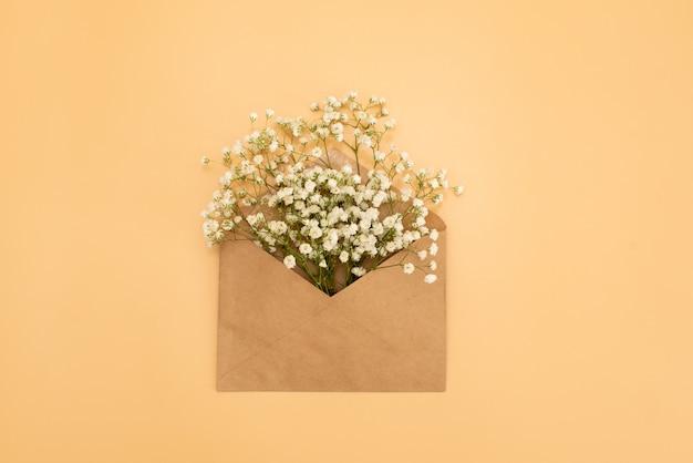Enveloppe ouverte avec des arrangements de fleurs sur fond rose, vue de dessus. concept de voeux festif Photo Premium