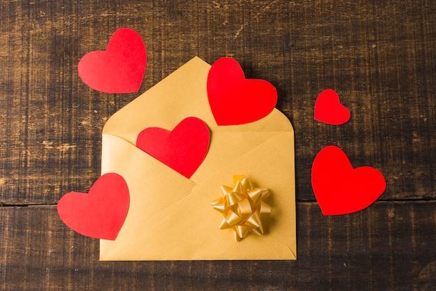 Enveloppe ouverte jaune avec coeur rouge et archet sur planche de bois texturée Photo gratuit