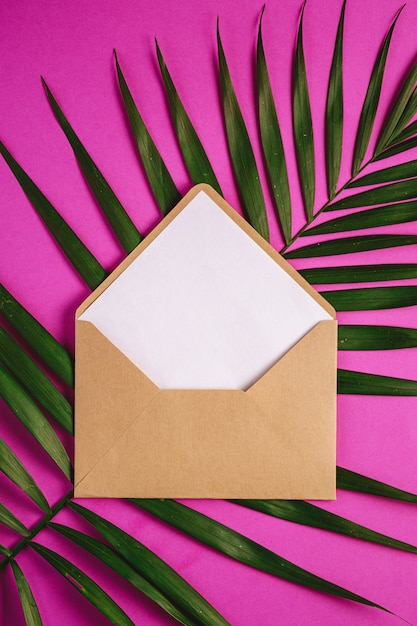 Enveloppe En Papier Brun Kraft Avec Une Carte Vide Blanche Sur Les Feuilles De Palmier, Fond Violet Rose, Lettre Vierge Maquette Photo Premium