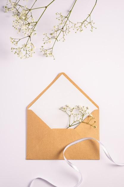 Enveloppe En Papier Brun Kraft Avec Carte Vide Blanche, Fleurs De Gypsophile Et Ruban De Tissu, Fond Blanc, Maquette Lettre Vierge Photo Premium