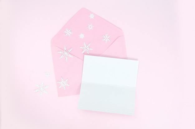 Enveloppe rose ouverte avec des flocons de neige de noël et une feuille de papier vierge Photo Premium