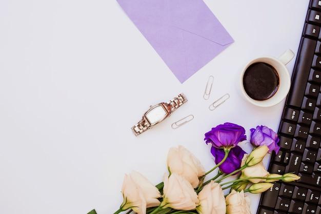 Enveloppe violette; montre-bracelet; trombone; tasse à café; clavier et eustoma fleurs sur fond blanc Photo gratuit