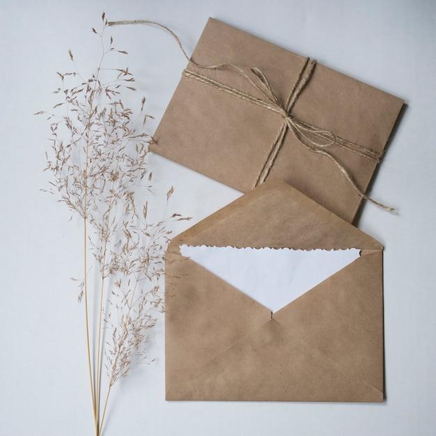 Enveloppes à fleurs sèches et kraft sur fond blanc. Photo Premium