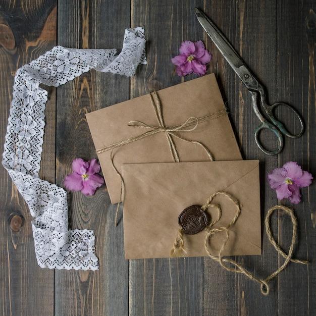 Enveloppes kraft beiges, vieux ciseaux et fleurs d'alto roses. invitation de mariage ou d'anniversaire ou concept et maquette de message. vue de dessus et pose à plat avec espace de copie Photo Premium