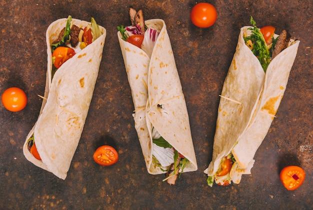 Enveloppez les tacos de boeuf mexicain à la tomate sur fond rouillé Photo gratuit