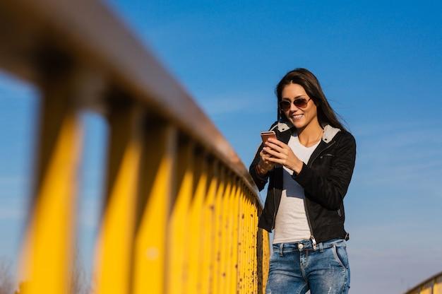 Envoyer des sms à l'extérieur de la belle jeune fille Photo Premium