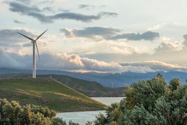 Éolienne sur la colline en face de ciel nuageux Photo Premium