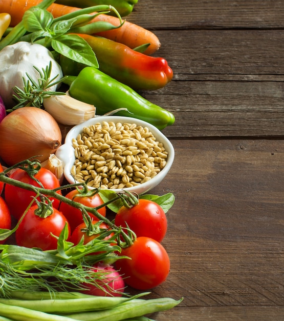 Épeautre Dans Un Bol Et Légumes Frais Sur Une Table En Bois Photo Premium