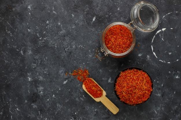 Épice de safran à la cuillère en bois, fond noir Photo gratuit