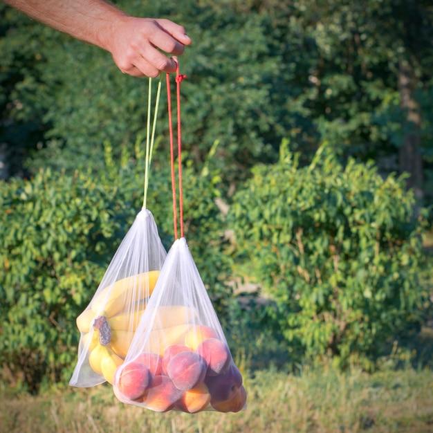 Épicerie maille avec des fruits à la main sur fond de nature Photo Premium