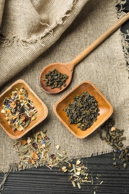 Épices à base de plantes sur bol en bois et cuillère sur le sac Photo gratuit