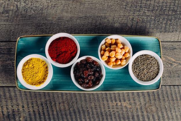Épices dans des petits bols blancs sur un fond en bois marron Photo Premium
