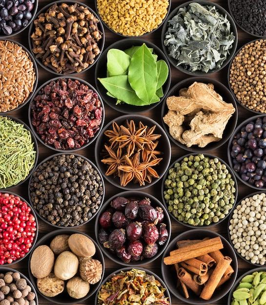 Épices et herbes lumineuses dans des tasses, vue de dessus. fond pour l'emballage avec des condiments européens. Photo Premium