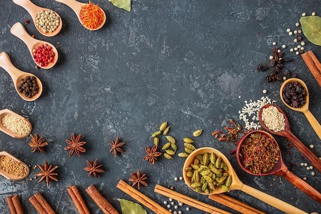 Des épices et des herbes sur pierre noire, plat poser. Photo Premium