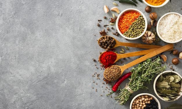 Épices et herbes, riz et divers haricots avec fond sur la vue de dessus de backgraund Photo Premium