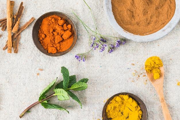 Épices près de cannelle et brindille de plante sur textile sur table Photo gratuit