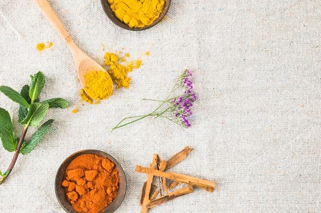 Épices près de cannelle et brindille de plante sur textile Photo gratuit