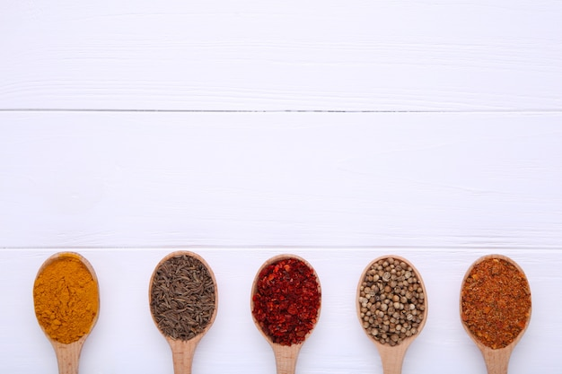 Les épices se mélangent sur des cuillères en bois sur un fond en bois blanc. vue de dessus Photo Premium