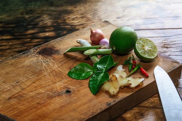 Les épices tom yum sont placées sur une planche à découper en bois marron et ont un bois marron foncé. Photo gratuit
