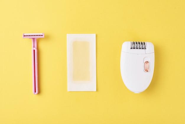 Épilateur, rasoir et bandes de cire sur une surface jaune Photo Premium