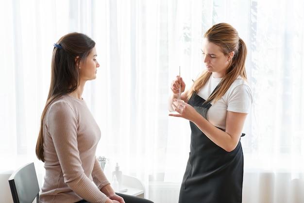 Épilation Des Sourcils Féminins Avec Des Pincettes Pendant La Correction Des Sourcils Dans Un Salon De Beauté Photo Premium