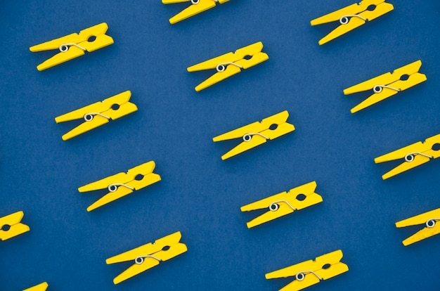 Épingles à linge jaunes plates sur fond bleu Photo gratuit
