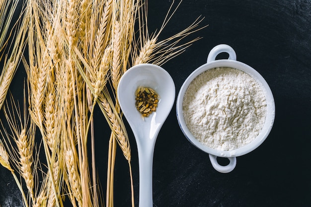 Épis de blé et farine sur fond noir Photo Premium