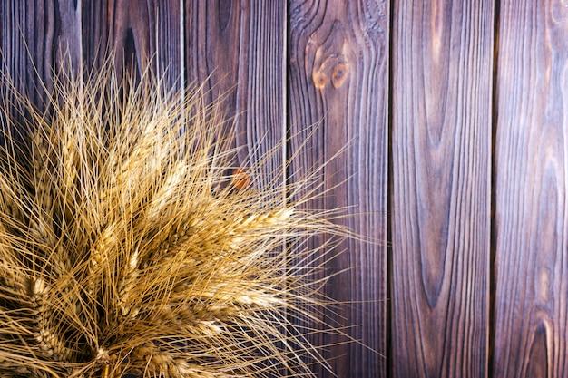Épis de blé sur fond en bois concept de récolte Photo Premium