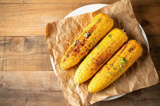Épis de maïs grillés sur fond de bois. Photo gratuit
