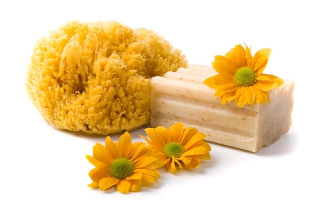 Éponge naturelle, savon et fleurs sur fond blanc Photo Premium
