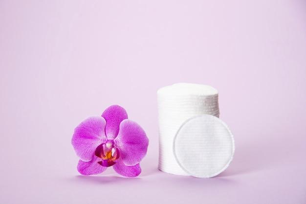 Éponges de coton dans un bocal en verre sur un fond rose avec une fleur d'orchidée Photo Premium