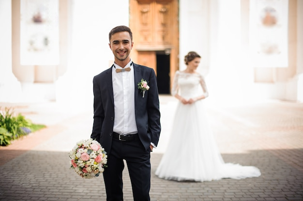 Époux Tenant Un Bouquet De Mariée Et Souriant Photo Premium