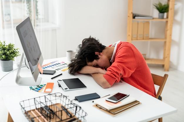 Épuisé Jeune Homme Pigiste Sieste Sur 24 Devant L'écran De L'ordinateur Parmi Les Fournitures De Travail Et Les Gadgets Photo Premium