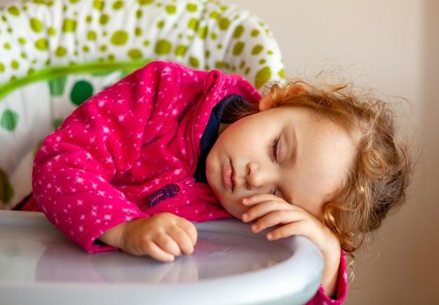 Épuisé petite fille endormie dans la chaise haute Photo Premium