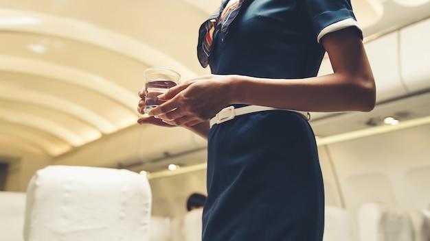 L'équipage De Cabine Sert De L'eau Au Passager En Avion Photo Premium
