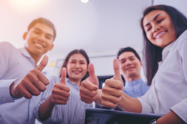 Équipe des activités montrant les pouces comme signe. fermer la main. Photo Premium