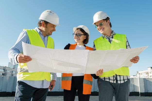 Équipe d'architecte ingénieur constructeurs sur le toit du chantier. Photo Premium