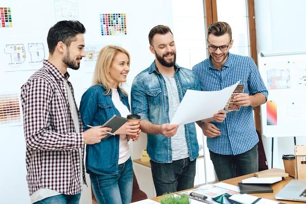Une équipe d'architectes concepteurs regarde blueprint. Photo Premium