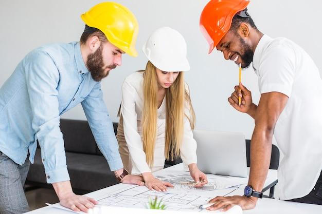 Équipe d'architectes travaillant sur un plan de construction Photo gratuit
