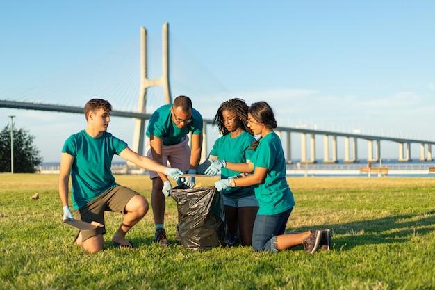 Équipe de bénévoles multiethnique retirant les déchets de l'herbe Photo gratuit
