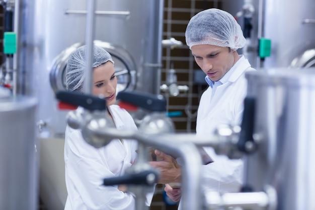 Une équipe de biologistes parlant et portant un filet à cheveux dans l'usine Photo Premium