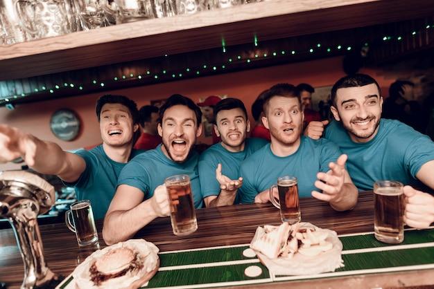 Équipe bleue amateurs de sport au bar boire de la bière. Photo Premium