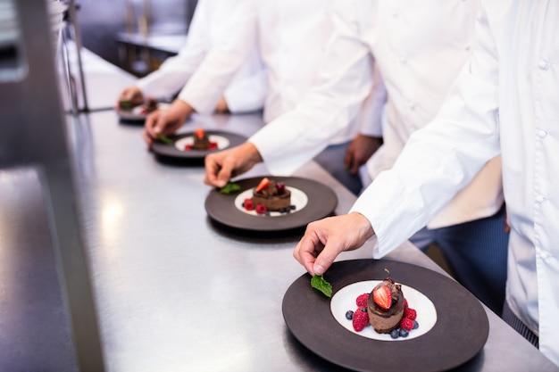 Équipe de chefs finissant des assiettes à dessert dans la cuisine Photo Premium