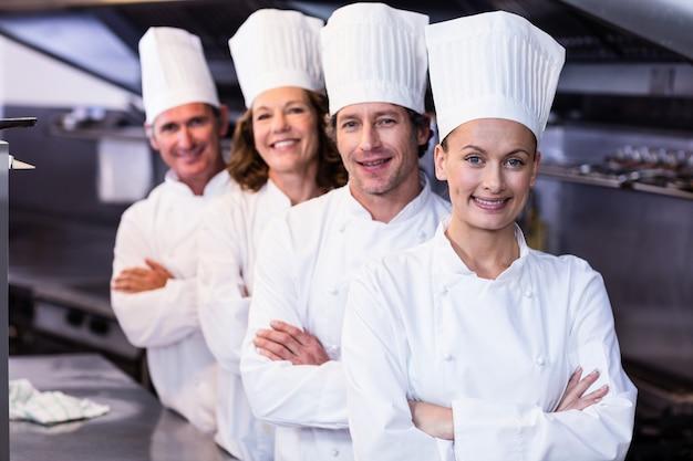 Équipe de chefs heureux debout ensemble dans la cuisine commerciale Photo Premium