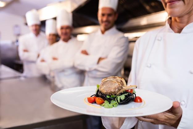 Équipe de chefs avec l'un présentant un plat Photo Premium